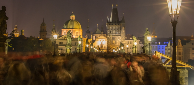 Night shot of blurred motion of crowd of people on Charles Bridge in Prague