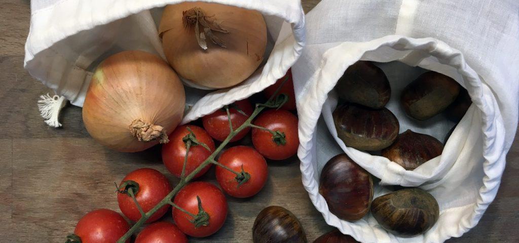Nachhaltig einkaufen mit Stoffbeutel, auch beim Plastikfasten: Stoffbeutel mit Zwiebeln, Tomaten, Kastanien