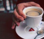Hand nimmt Kaffee: bitte keine kleinen Zuckertüten