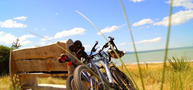 Fahrradurlaub, Fahrräder lehnen an Bank am Strand