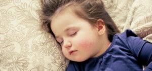 Mädchen schläft auf Kindermatratze