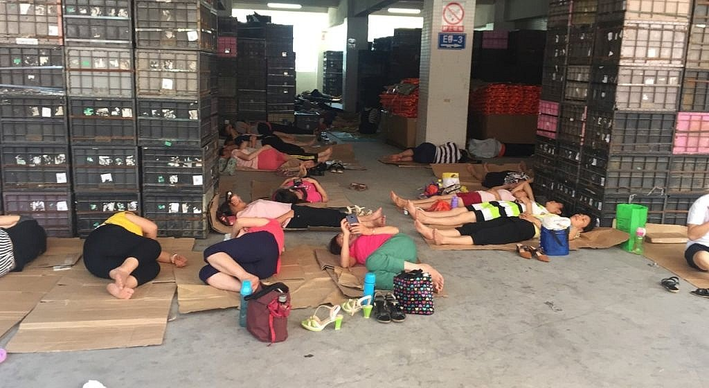 Spielzeug Produktion in China, erschöpfte ArbeiterInnen schlafen auf dem Fabrikboden