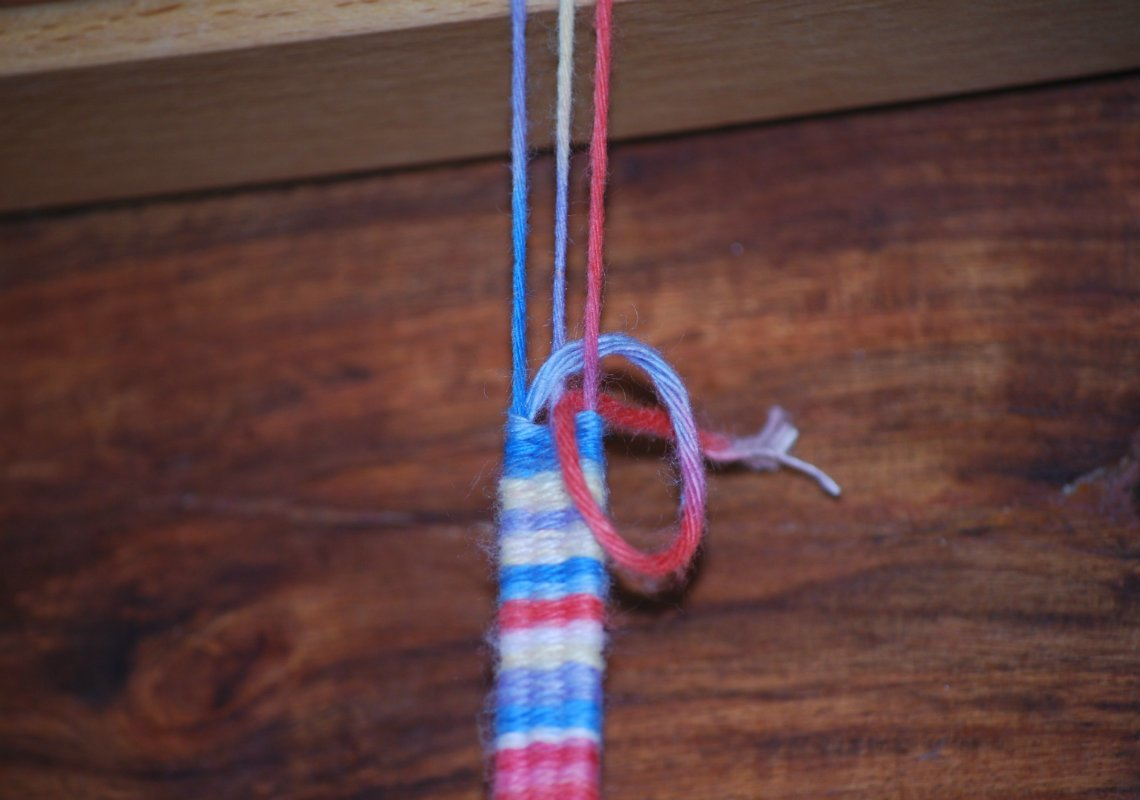 An beiden Enden des Armbandes machst du eine Schlaufe, um die Fäden zu fixieren.