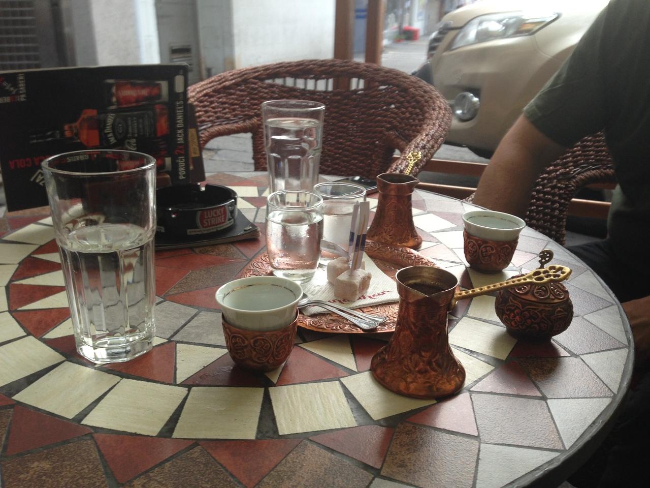Türkischer Kaffee serviert im Kännchen mit Lokum und einem Glas Wasser.